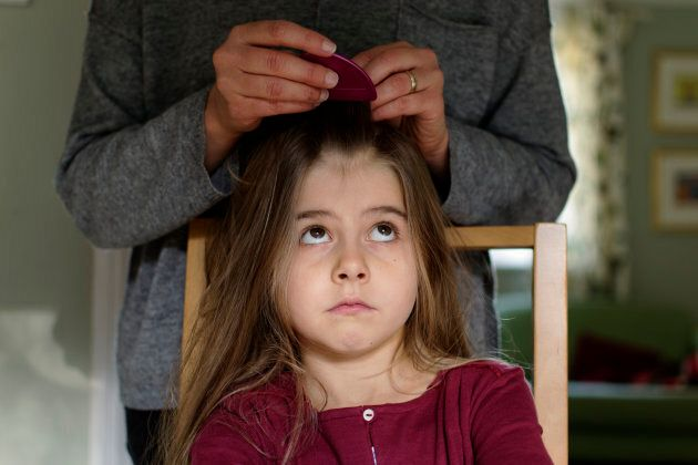 A mother checking her daughter's hair for head lice using a nit comb.