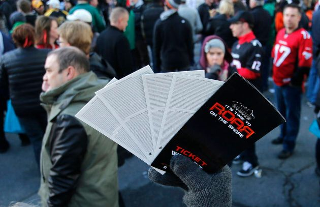 A scalper tries to sell tickets ahead of the CFL's 102nd Grey Cup football championship between the Calgary...