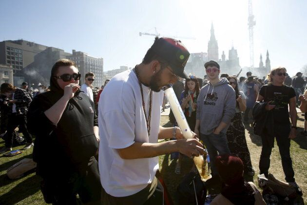 People smoke marijuana during an annual 4/20 rally on Parliament Hill in Ottawa on April 20,