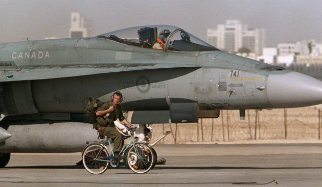 A Canadian CF-18 pilot prepares to take off, as a member of the ground crew pedals his bicycle past the...