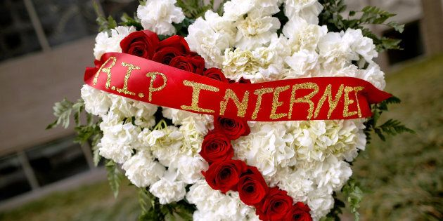 A funeral flower arrangement is set up outside the Federal Communication Commission building during a protest against the end of net neutrality rules on Thursday.