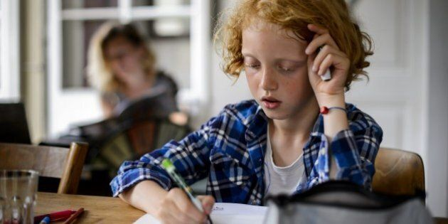 Swiss boy Leon, 9, does his homework on June 20, 2013 in his home in Moudon, western Switzerland. AFP...
