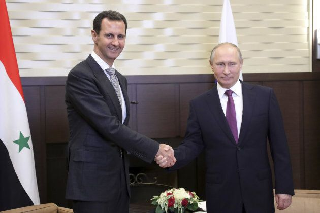 Russian President Vladimir Putin shakes hands with Syrian President Bashar al-Assad during a meeting...