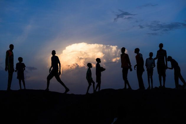 Children gather on a bank at sunset in the Protection of Civilians (PoC) site in Bentiu, South Sudan, Sunday 30 April 2017.