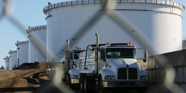 Dump trucks parked near crude oil tanks at Kinder Morgan's North 40 terminal project in Sherwood Park, near Edmonton, Alta. on Nov. 13, 2016. Canadian oil prices have plunged amid a supply glut.