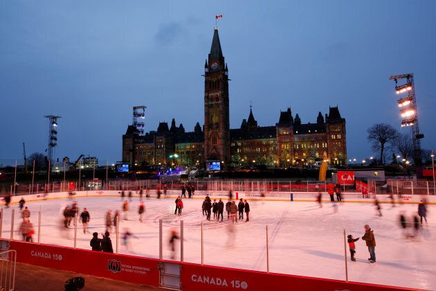 People skate on the Canada 150 ice rink on the front lawn of Parliament Hill in Ottawa on Dec. 7, 2017.