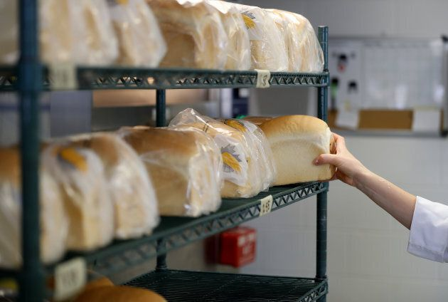 A specialist reaches for a loaf of bread on a shelf at the Canadian International Grains Institute lab...