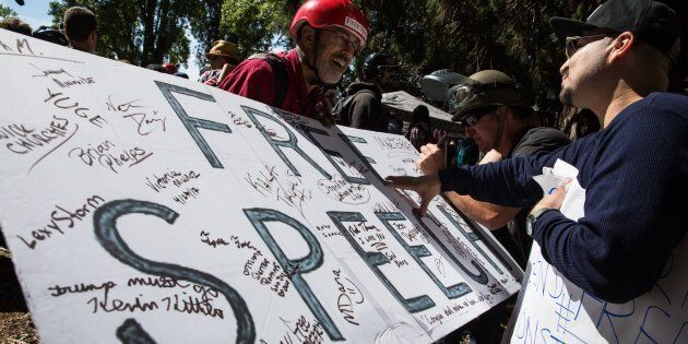 Jeff Barnes (left) of Alameda, Calif., invites people to sign a free speech sign during a pro-Donald...
