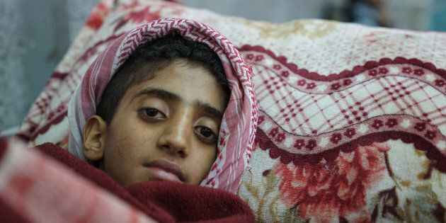 A young boy lies in the emergency room awaiting treatment for suspected cholera at the Al-Joumhouri Hospital,...