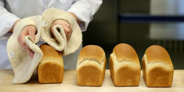 A specialist places loaves of bread made from pulse flour containing yellow split peas on a table at...