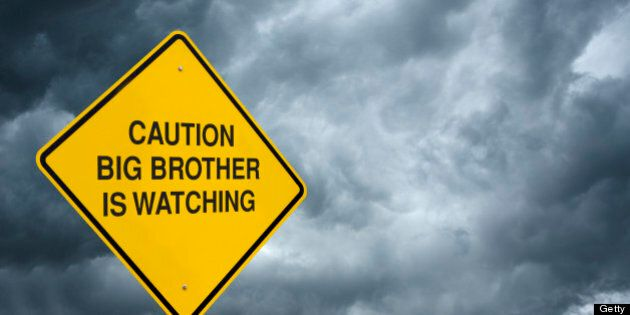 A caution sign in front of storm clouds warning of 'Big Brother is