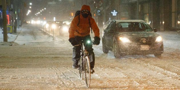 A cyclist commutes during a winter snowstorm in Toronto on Dec. 15,