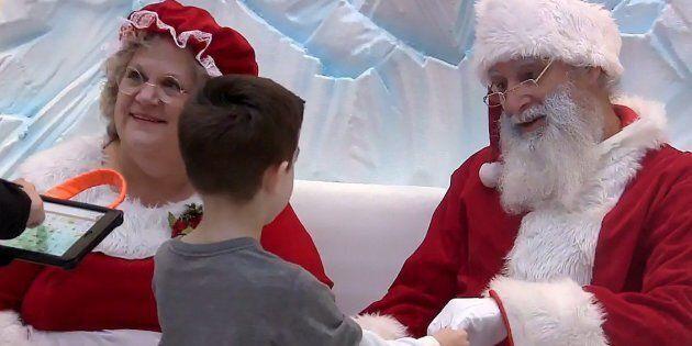 Tyson Lehr meets Santa, Robert Blais, and Mrs. Claus, Cheryl Agostino, while his mother Bethany Lehr...