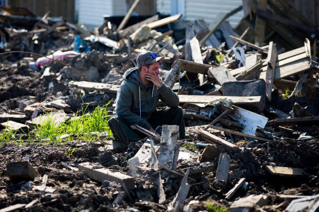 A resident looks over the damage in Fort McMurray's Timberlea neighbourhood as thousands of evacuees...