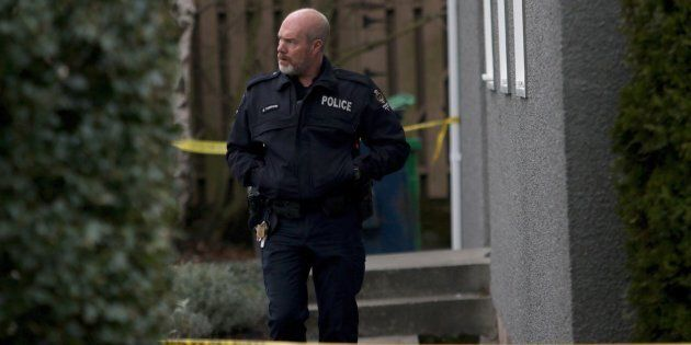 An Oak Bay officer leaves the apartment building where the bodies of sisters aged four and six were found...