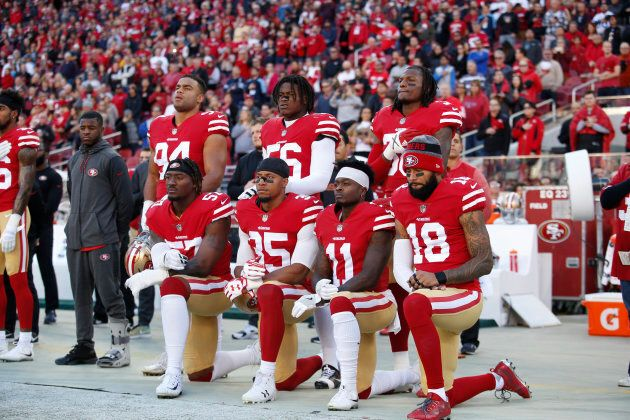 Eli Harold, Eric Reid, Marquise Goodwin, and Louis Murphy of the San Francisco 49ers kneel during the anthem as Solomon Thomas, Reuben Foster, and Adrian Colbert stand with them in support, prior to the game against the Tennessee Titans on Dec. 17, 2017.