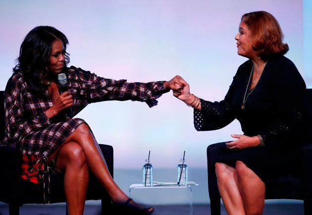 Former First Lady Michelle Obama holds hands with poet Elizabeth Alexander at the Obama Foundation Summit...
