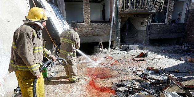 Afghan fire fighters spray water to remove the bloodstains at the site of a suicide attack in Kabul,...