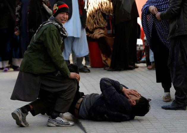 Afghan men mourn inside a hospital compound after a suicide attack in Kabul Dec. 28,