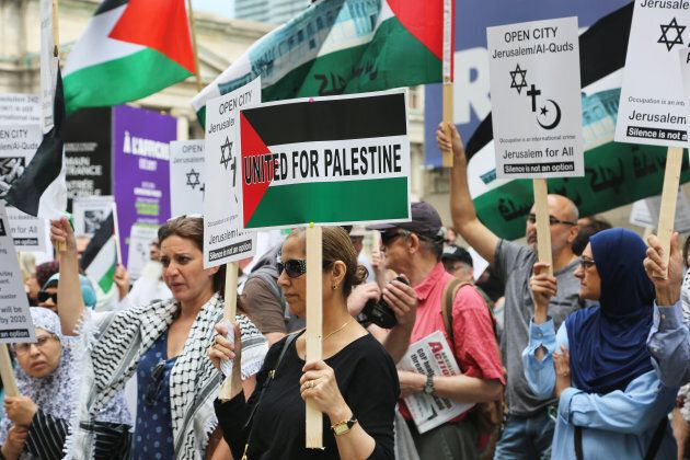 Protestors hold signs during a pro-Palestinian demonstration in Toronto on July 29, 2017.