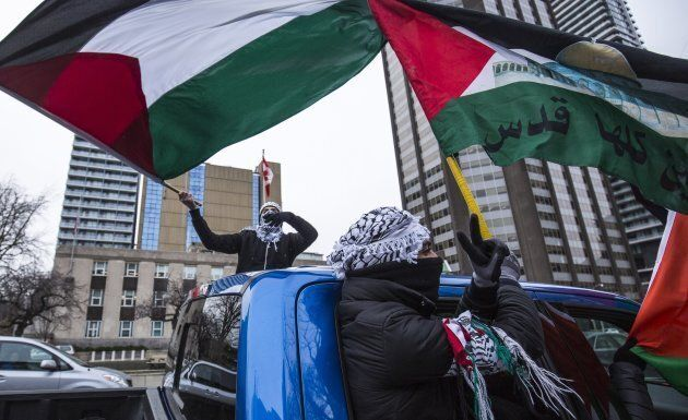 Protesters wave Palestinian flags in Toronto on Dec. 9, 2017, as they walk across University Avenue in...
