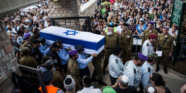 An honour guard caries the coffin of Israeli Lt. Hadar Goldin during his funeral on Aug. 3, 2014 in Kfar-saba,...