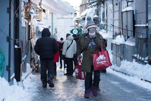 People walk down an icy street in Quebec City on Dec. 27,