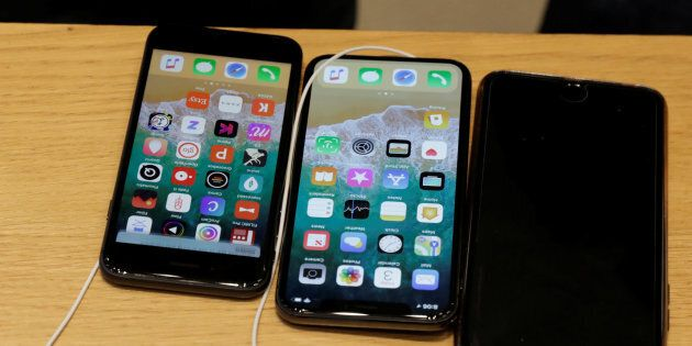 An Apple iPhone X model (C) is seen next to older models of iPhone on a table at an Apple store in New...