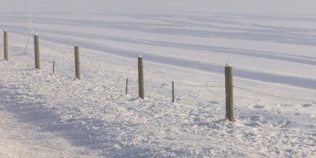 A fence in a snow-covered field in northern Canada.
