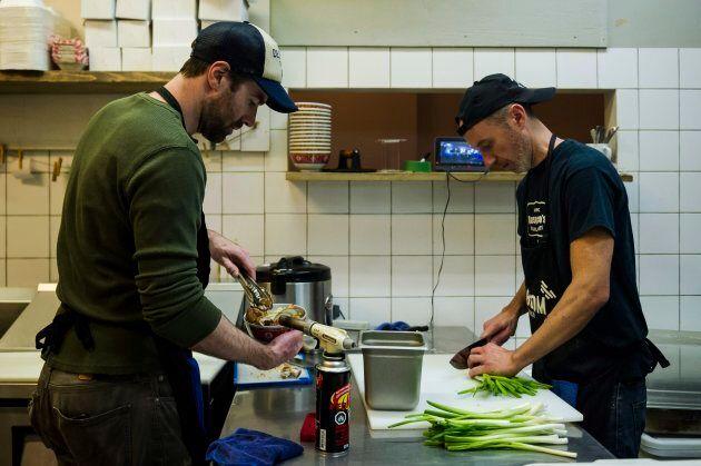 Chris Stevens, owner of Kaboom Chicken restaurant, prepares an order with employee Rene Carlsen in Toronto...