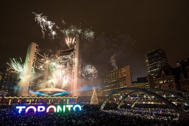 Fireworks light up the sky at Toronto's City Hall, Nathan Phillips Square, as the clock strikes midnight...