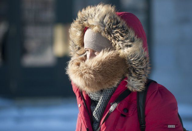 A person walks with their face covered on a cold day in Quebec City on Dec. 27,