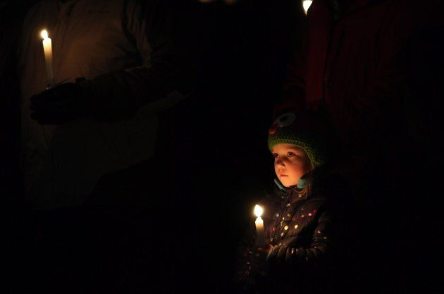 Viella Trausch, a classmate of Aubrey Berry, 4, and her sister Chloe, 6, holds a candle during a vigil...