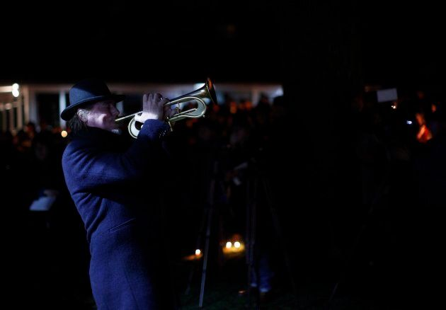 A man plays Hallelujah with his trumpet in support and memory of Aubrey Berry, 4, and her sister Chloe,...
