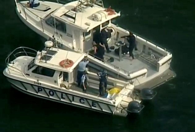 Police vessels are seen after a seaplane crashed into a Sydney river, killing six people on a