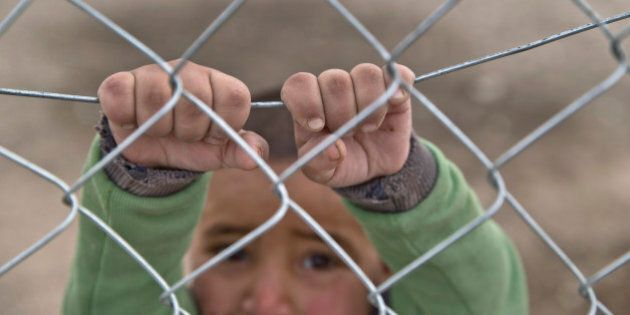 A Syrian Kurdish refugee child from the Kobani area, holds on to a fence at a camp in Suruc, on the Turkey-Syria...
