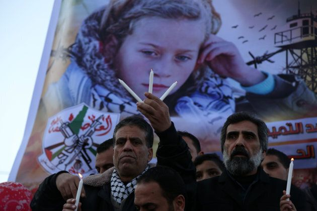 Palestinians hold candles during a support demonstration for Ahed Tamimi in Gaza City on Jan. 8,