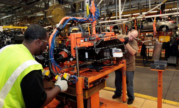 Ford assembly workers install a battery onto the chassis of a Ford Focus electric vehicle.