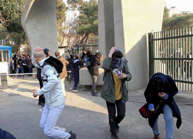 In this photo taken on Dec. 30, 2017, by an individual not employed by the Associated Press and obtained by the AP outside Iran, university students run away from stones thrown by police during an anti-government protest inside Tehran University, in Tehran.