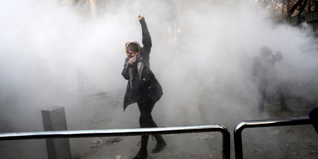 A university student attends a protest inside Tehran University while a smoke grenade is thrown by anti-riot...