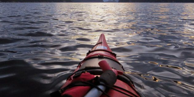 This photo taken Aug. 15, 2014 shows the view at dusk shows a sunset kayak outing, along the Saguenay fjords near Tadoussac, Quebec, a lively town visited by more Europeans than Americans.  Here, the Saguenay River converges with the mighty St. Lawrence in saline waters frequented by whales. The commanding Saguenay fjords are a playground for hikers, nature lovers and kayakers as well as for cyclists who come from afar to bike Quebec's Route Verte bicycle network.  (AP Photo/R.M. Green)