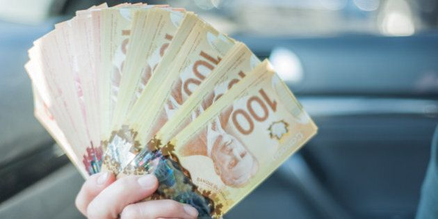 A woman counts $100 Canadian notes/bills before making a large