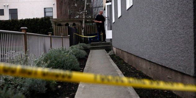 An Oak Bay officer enters the apartment building where the bodies of sisters aged four and six were found...