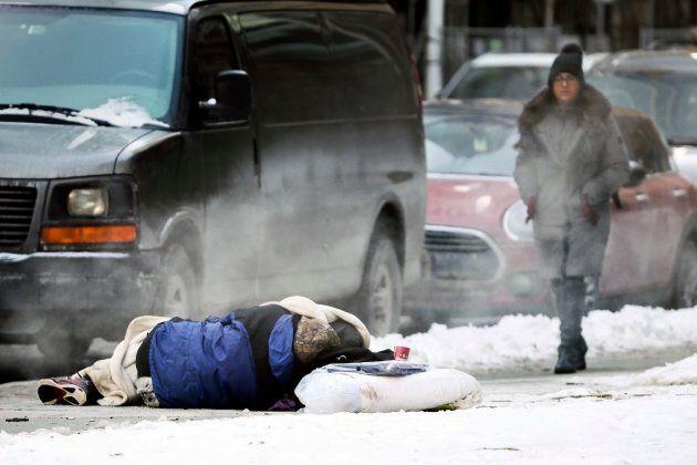 A pedestrian walks near a sleeping homeless man at the corner of James and Albert Sts., Jan. 4,