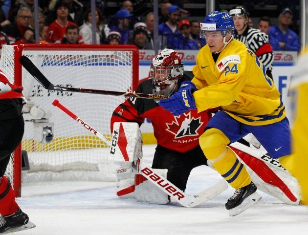 Sweden forward Lias Andersson skates past Canada goalie Carter Hart during the first period in the gold...
