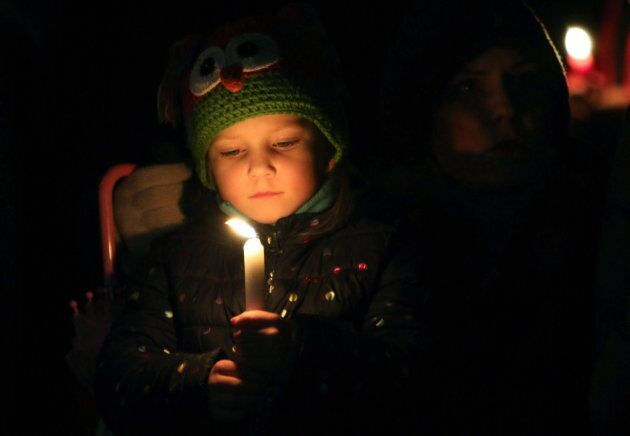 Viella Trausch, a classmate of Aubrey and Chloe Berry holds a candle during a vigil on Dec. 30,