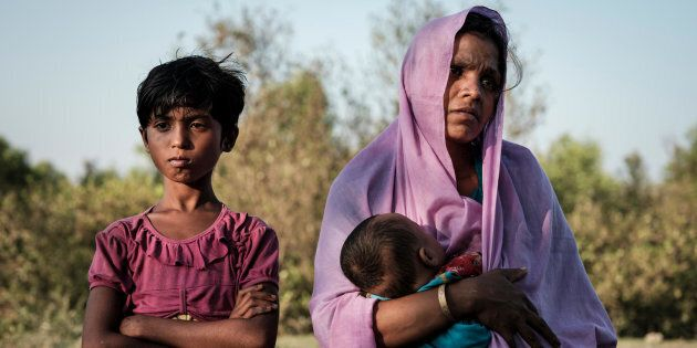 Rohingya refugee Mariom Khatun, 25, holds her baby Firuz Ahmed, 5 months, as they rest on the banks of...