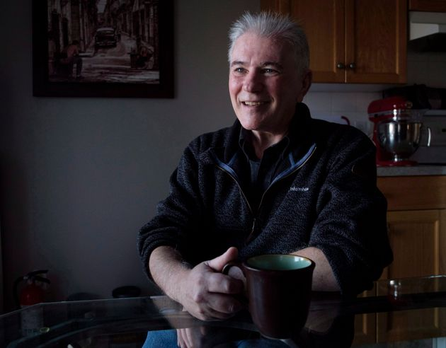 Roger Marple, who was diagnosed with early-onset Alzheimer's in 2015 at age 57, sits at a kitchen table...