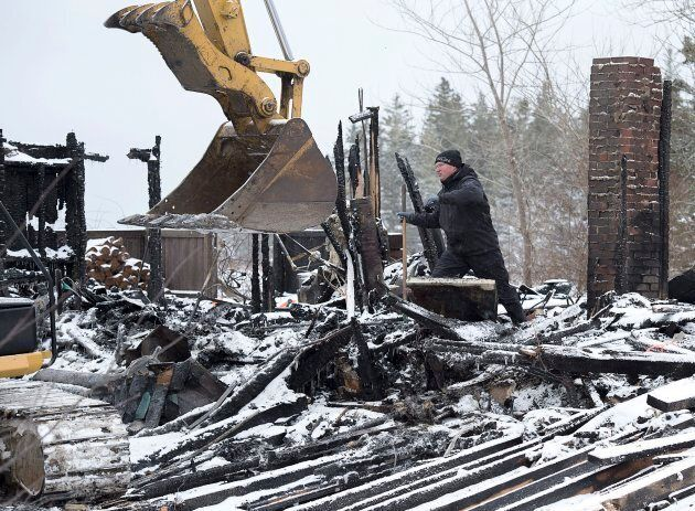 AN RCMP officer searchs the scene of a house destroyed in a weekend fire in Pubnico Head, N.S. on Jan....