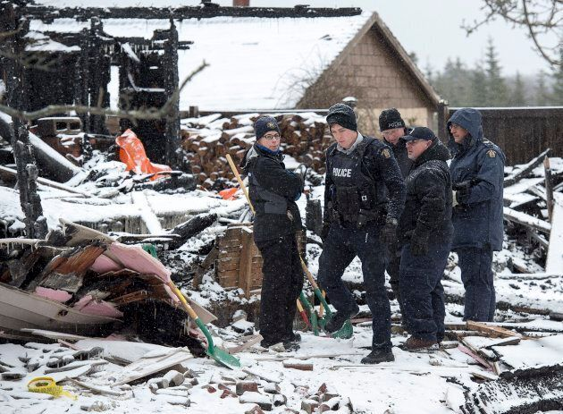 RCMP officers and a representative of the Medical Examiner's office search the scene of a house destroyed...